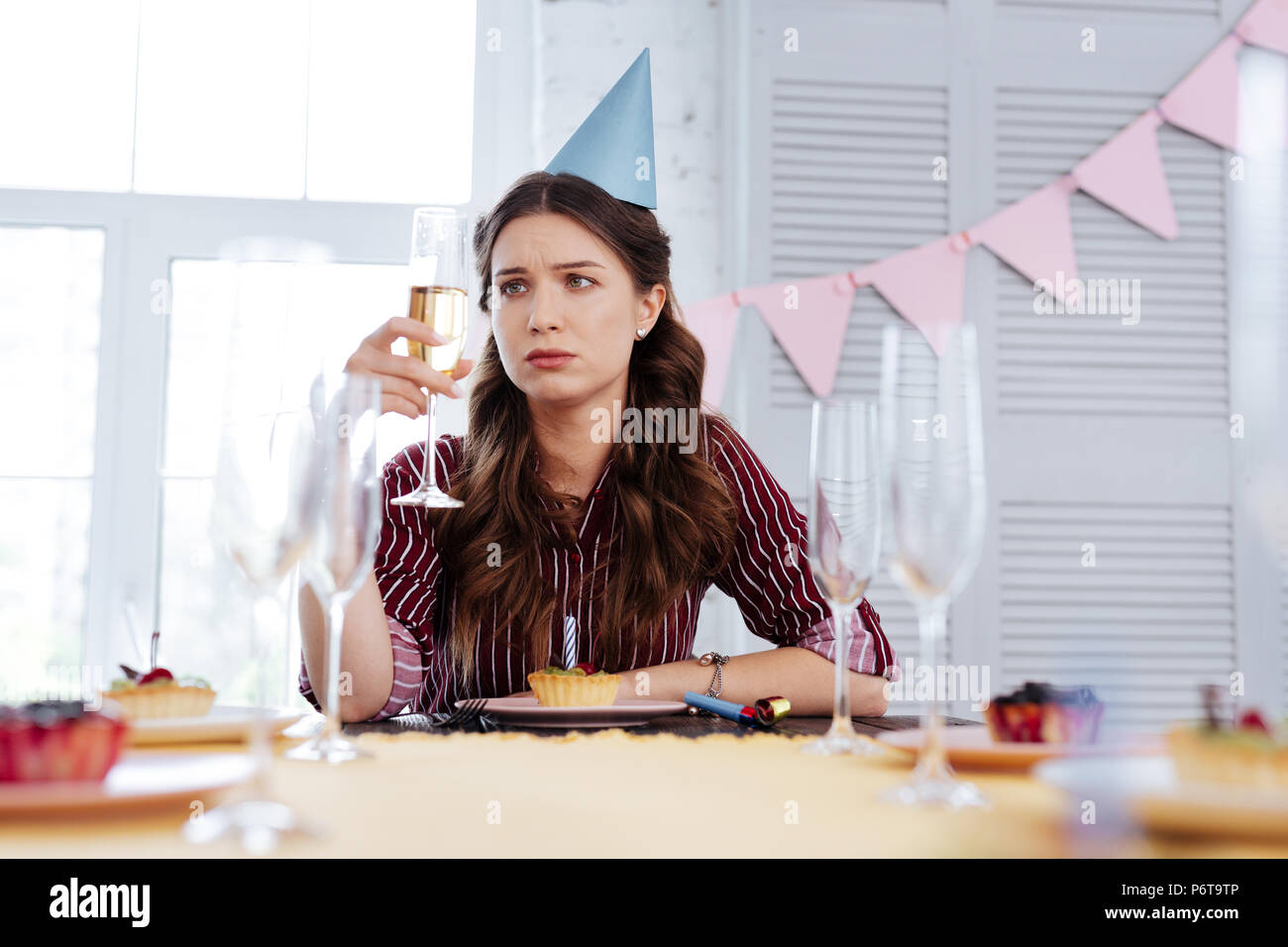Woman feeling pessimistic at birthday party - Stock Image