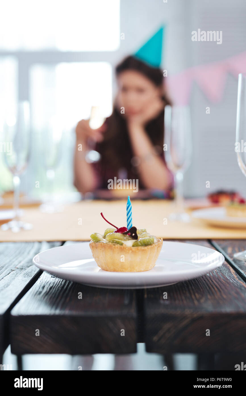 Woman looking at nice sweet dessert at birthday party - Stock Image
