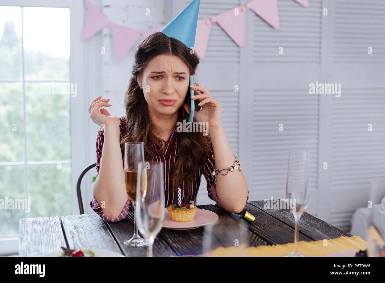 Emotional woman calling her guests on birthday - Stock Image