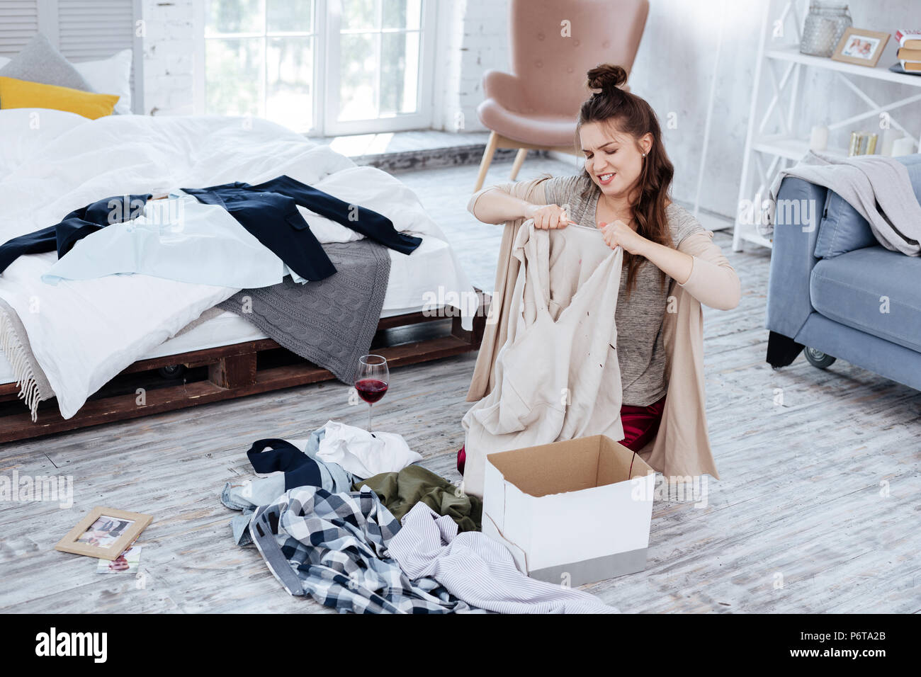 Angry nervous woman tearing clothes of husband after treason - Stock Image