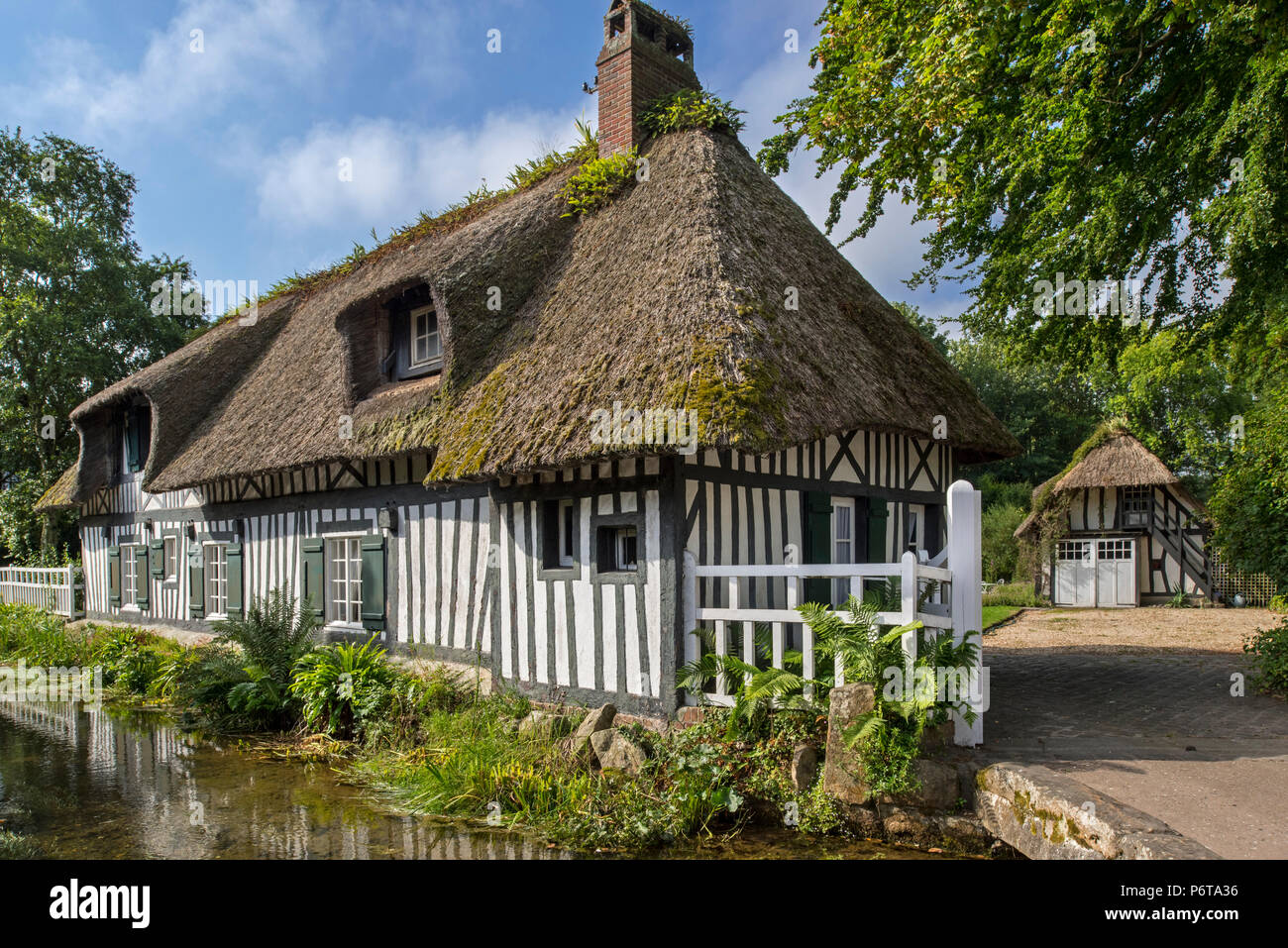 Timber-framed house with thatched roof along the river Veules, France's shortest river at Veules-les-Roses, Seine-Maritime, Côte d'Albâtre, Normandy - Stock Image