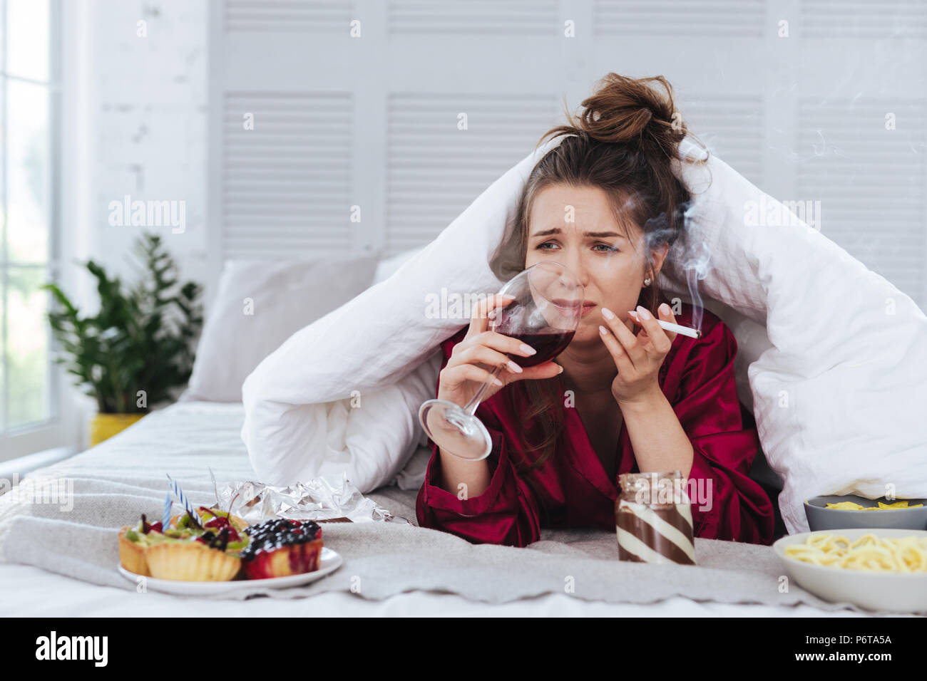 Heartbroken woman smoking while lying in bed drinking wine - Stock Image