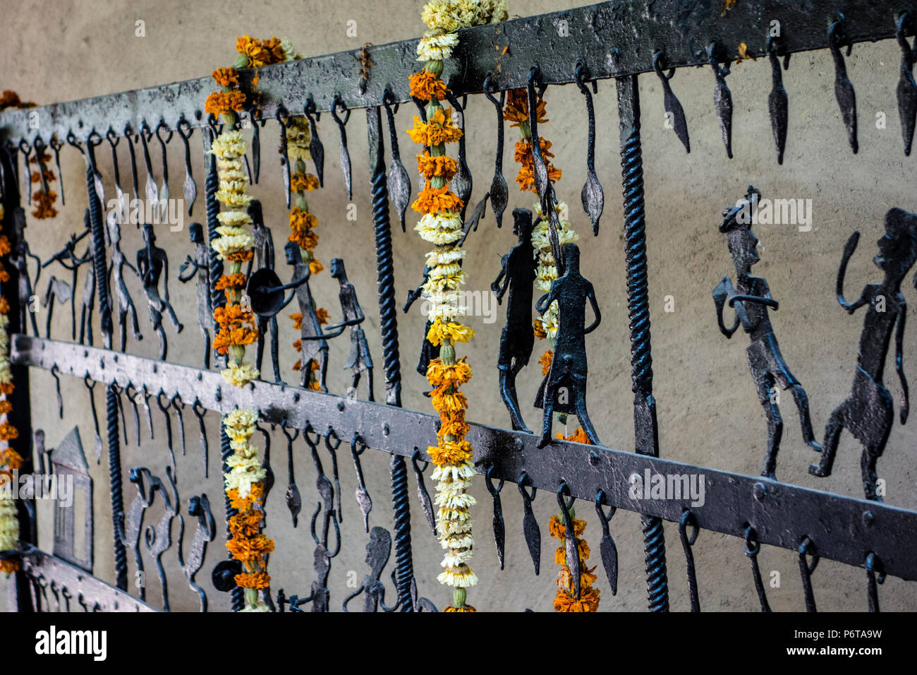 Exhibit of a wrought iron gate or fence from Bastar, Chhattisgarh hung with flower garlands in the National Crafts Museum, New Delhi, India - Stock Image