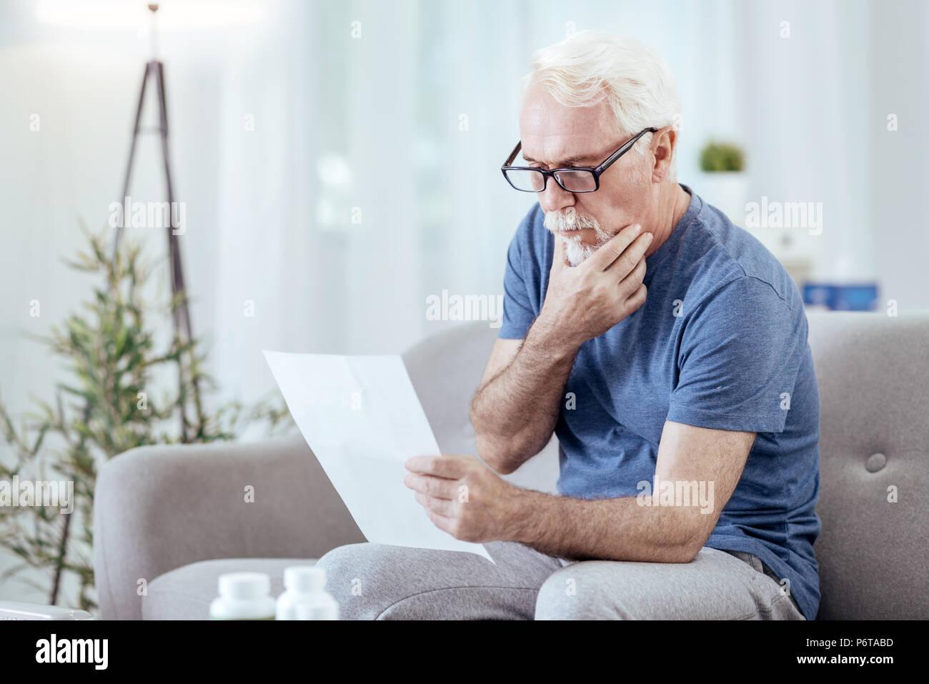 Pensive senior man studying instruction - Stock Image
