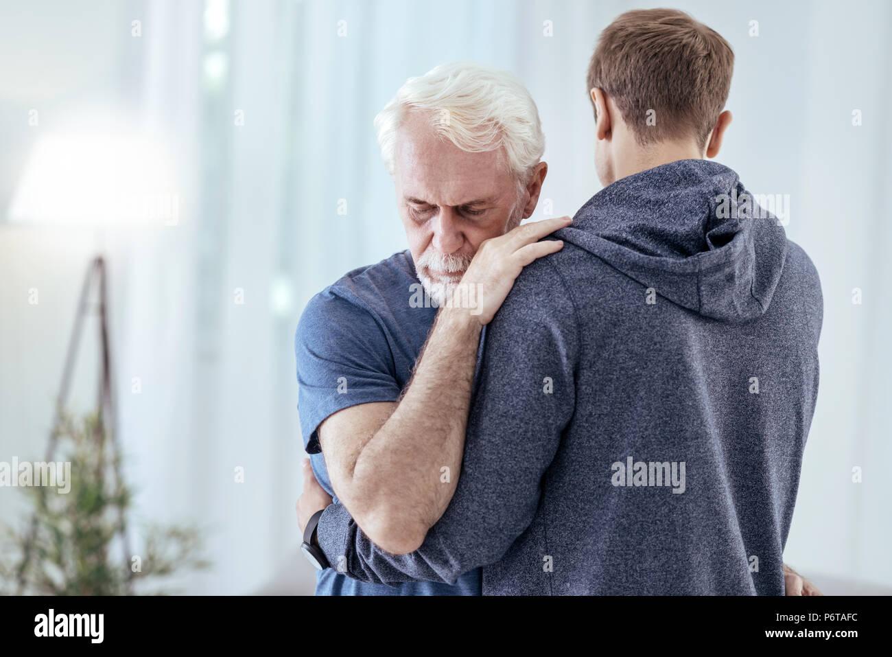Young man encouraging senior man - Stock Image