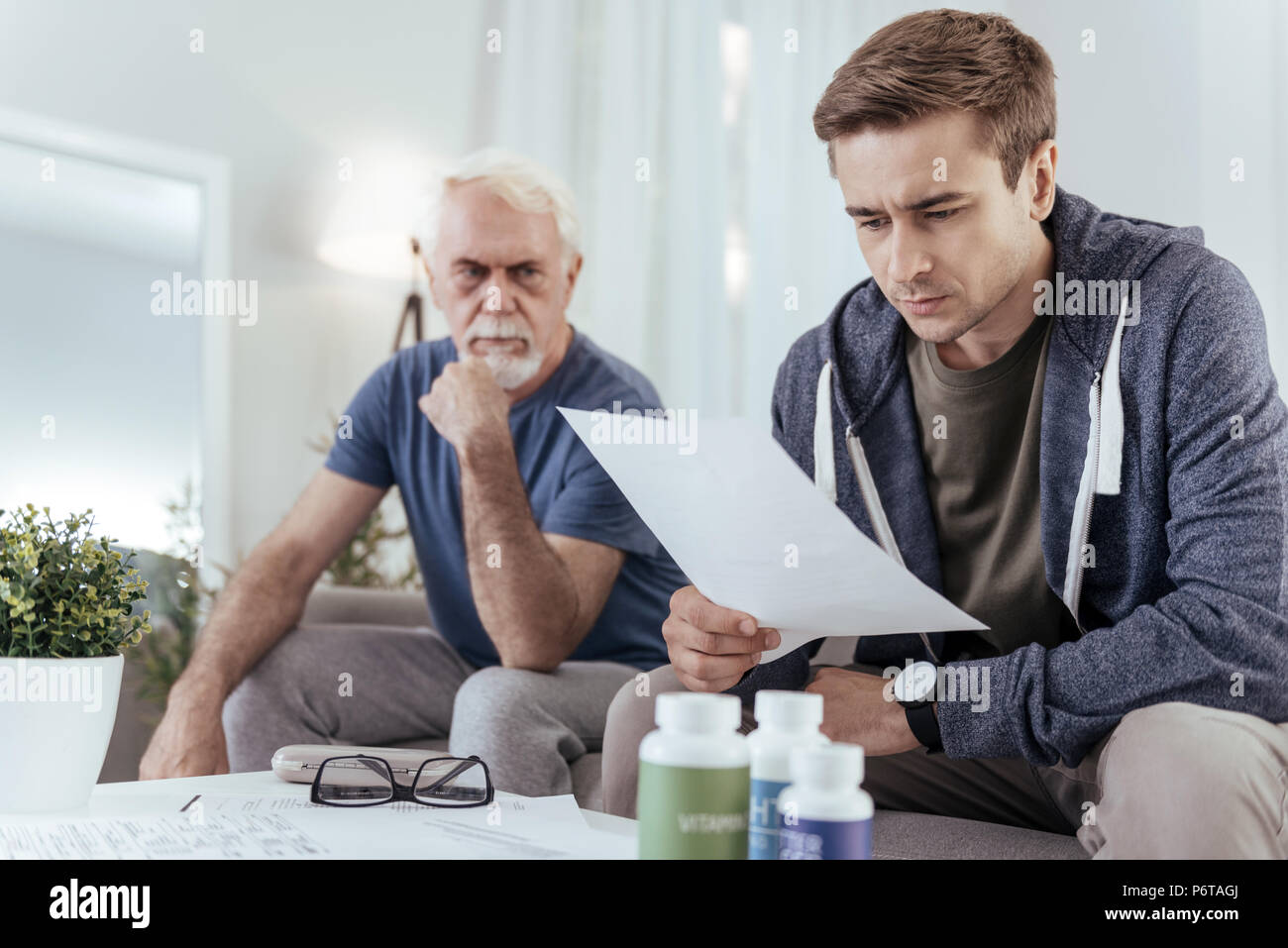 Uneasy pleasant man studying diagnosis - Stock Image