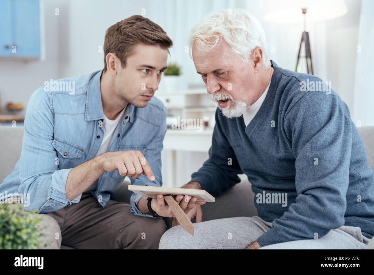 Astonished senior man reminiscing past - Stock Image