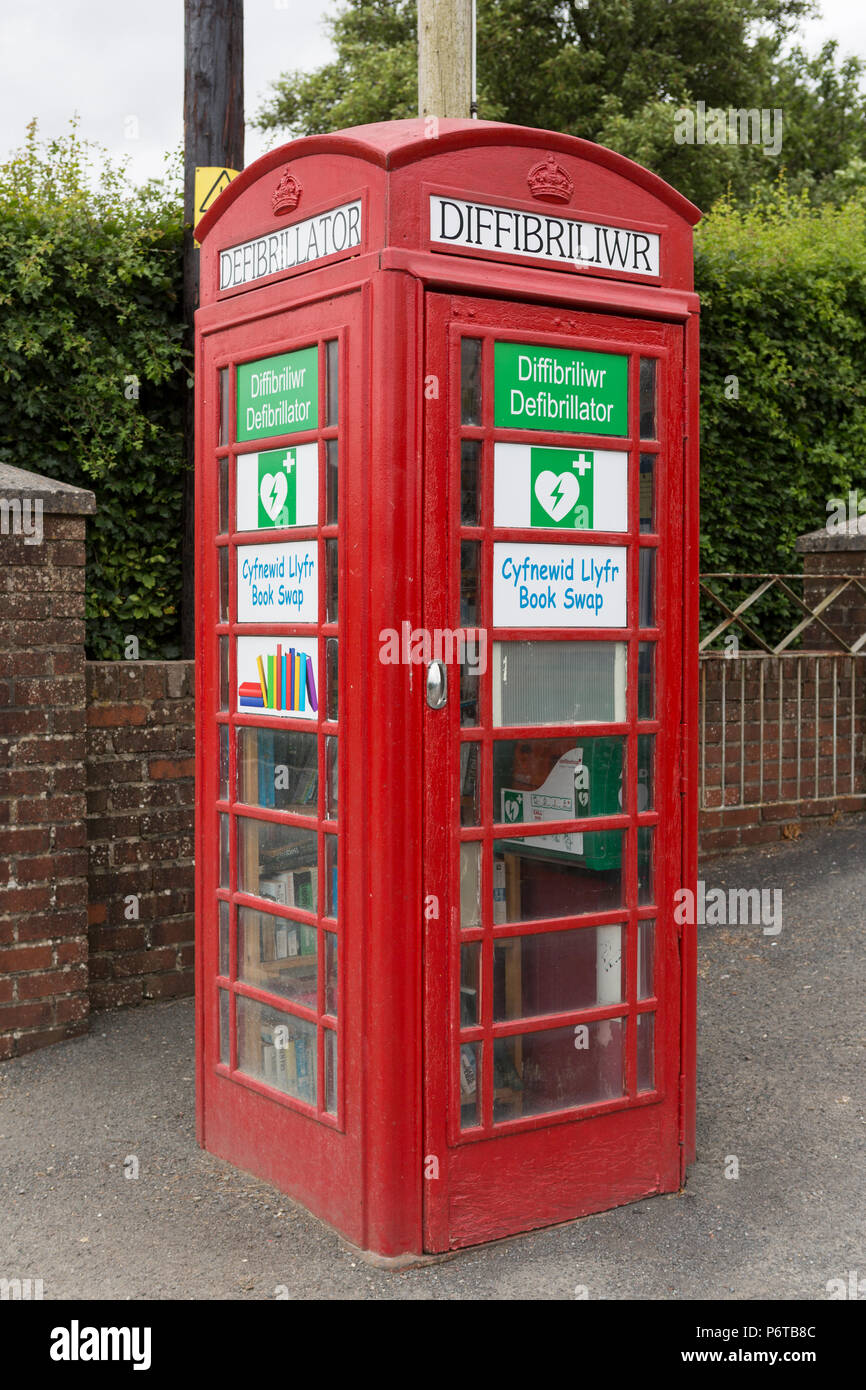 New and original use for old British red telephone box housing a defibrillator and second hand book swap - Stock Image
