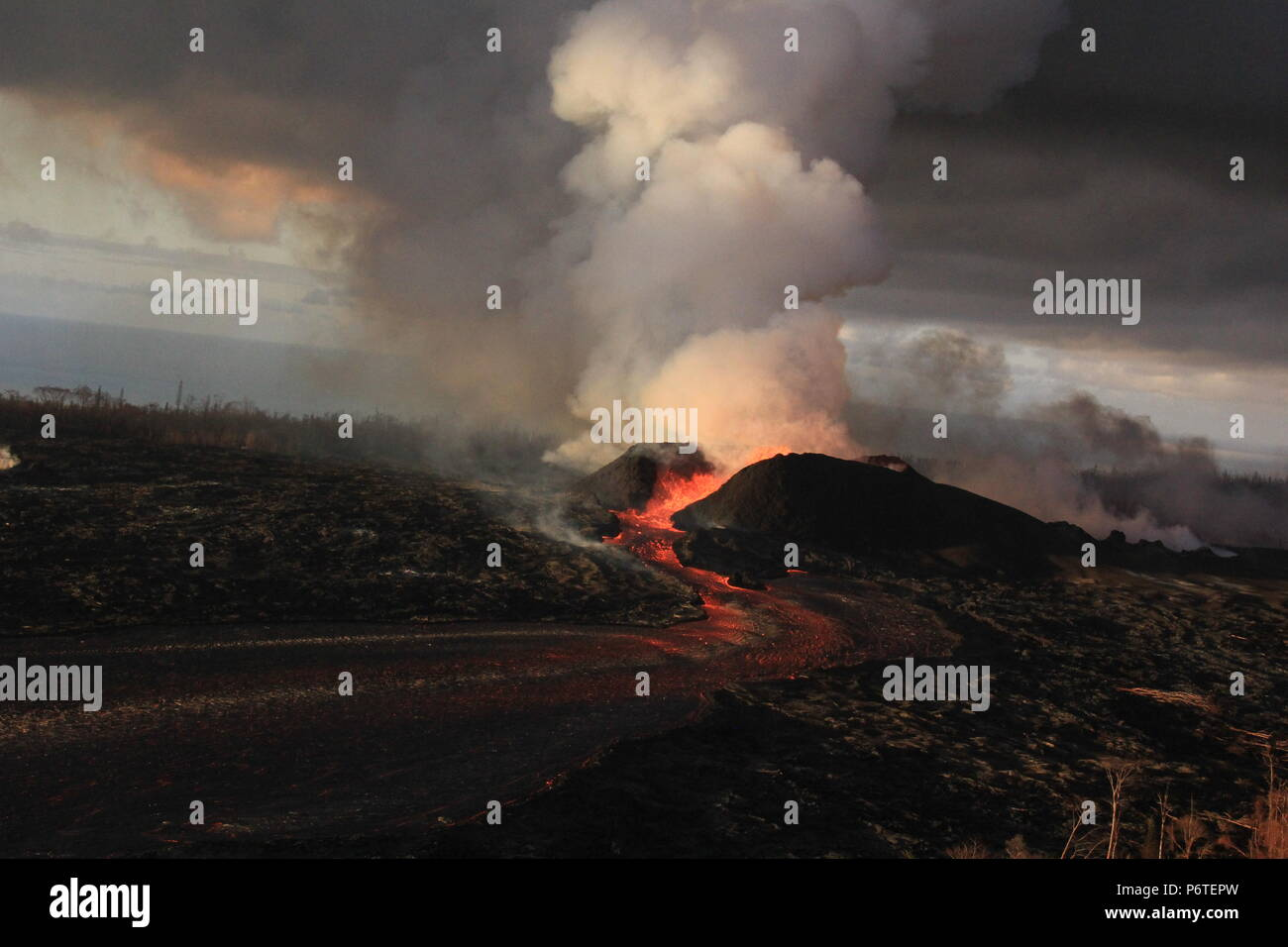 Lava fountains continue to spew magma from the 180 foot tall spatter cone with lave flowing into an open channel at fissure 8 caused by the eruption of the Kilauea volcano June 30, 2018 in Hawaii. The recent eruption continues destroying homes, forcing evacuations and spewing lava and poison gas on the Big Island of Hawaii. - Stock Image