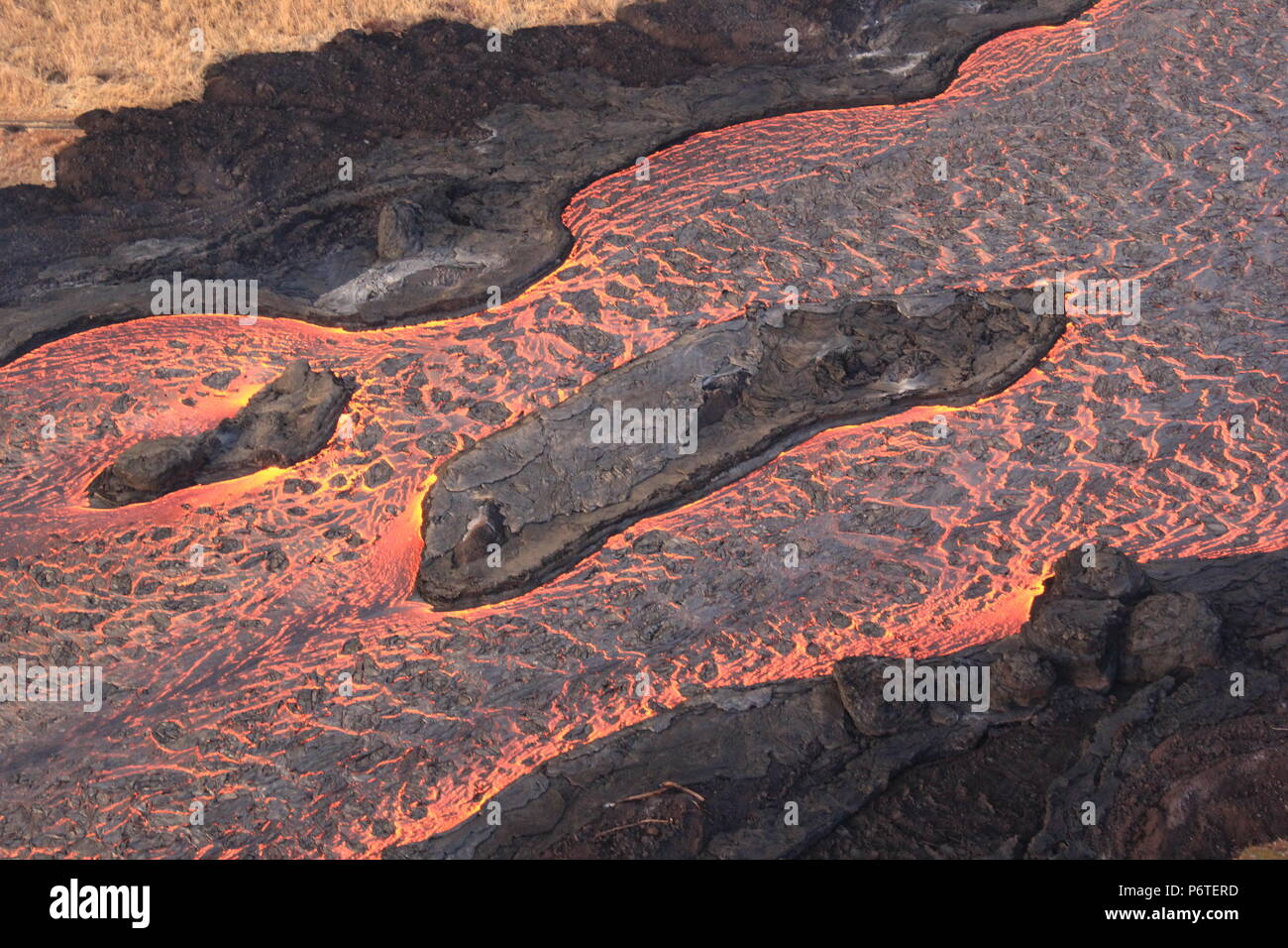 Lava flowing into an open channel from fissure 8 travels to the sea 8 miles away caused by the eruption of the Kilauea volcano June 30, 2018 in Hawaii. The recent eruption continues destroying homes, forcing evacuations and spewing lava and poison gas on the Big Island of Hawaii. - Stock Image