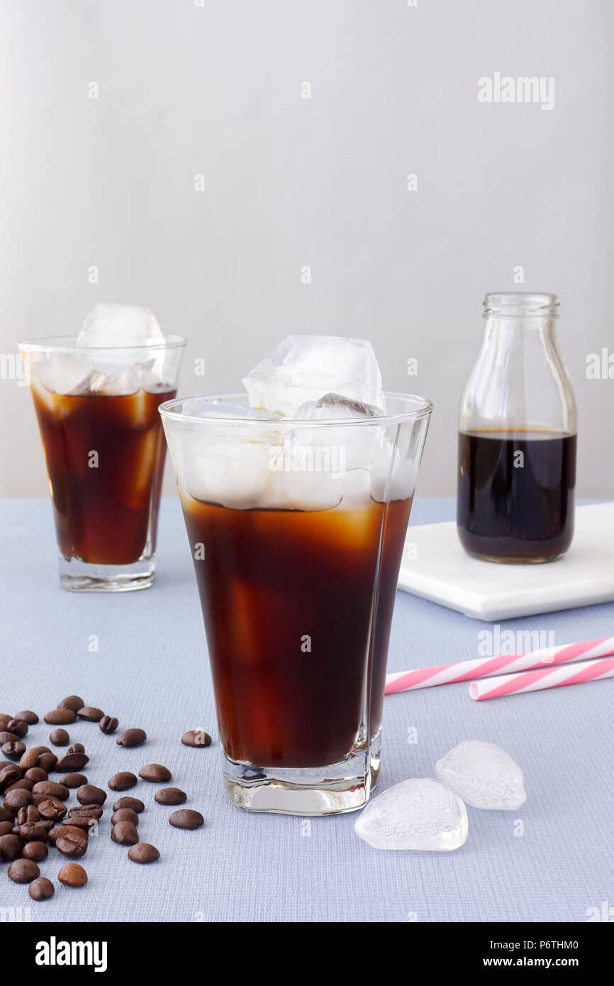 Composition of two highball tumblers filled with iced coffee and ice cubes. - Stock Image