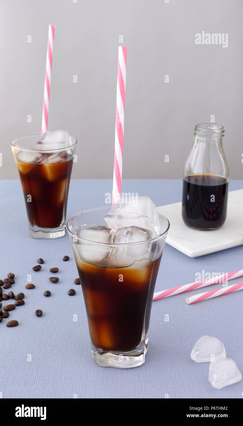 Two glasses with straws, ice cubes and cold brew coffee on a table and a bottle of cold brew coffee concentrate on white marble board in the backgroun - Stock Image