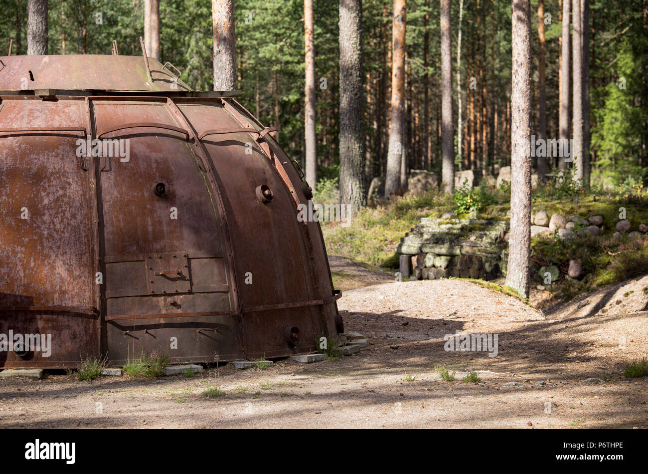 Old rusty dome shaped military structure in pine wood in historic Salpalinja defense line, Miehikkälä, Finland - Stock Image