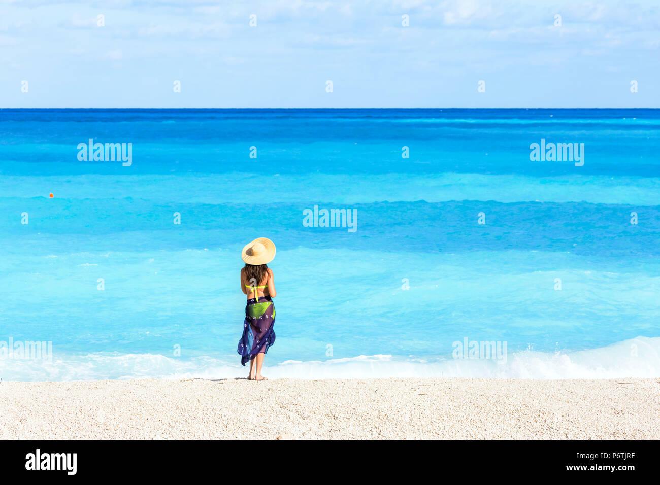 Woman with straw hat on famous Myrtos beach. Kefalonia, Greek Islands, Greece (MR) Stock Photo