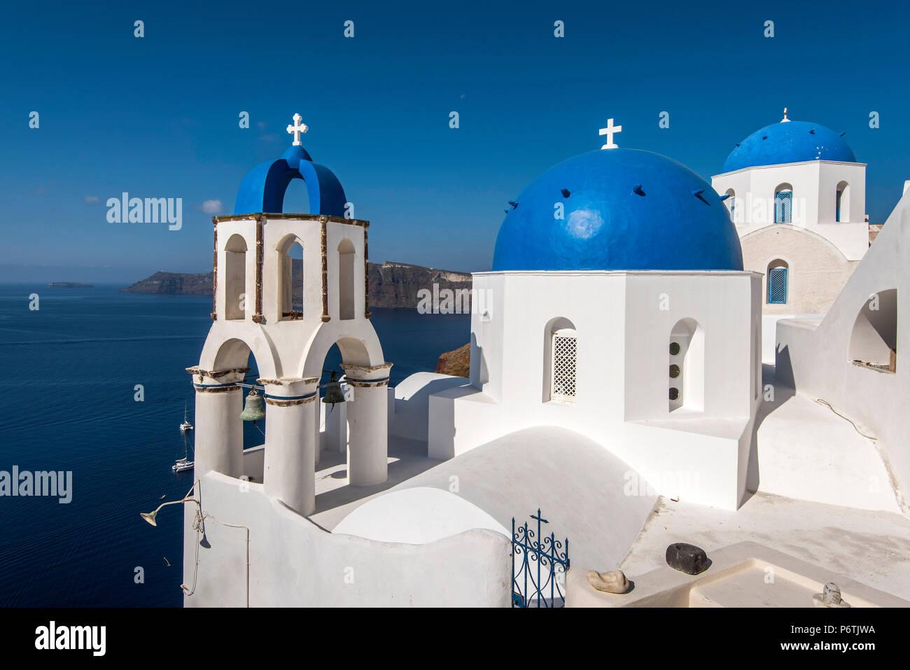 Greek orthodox church with blue domes in Oia, Santorini, South Aegean, Greece - Stock Image