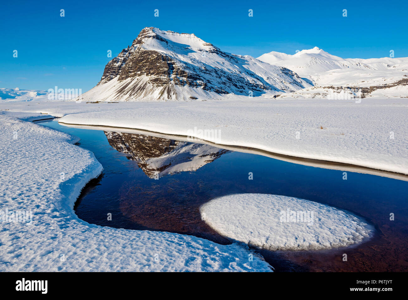 Iceland, Europe. Mountains mirroring in a crystal clear water surrounded by snow. - Stock Image