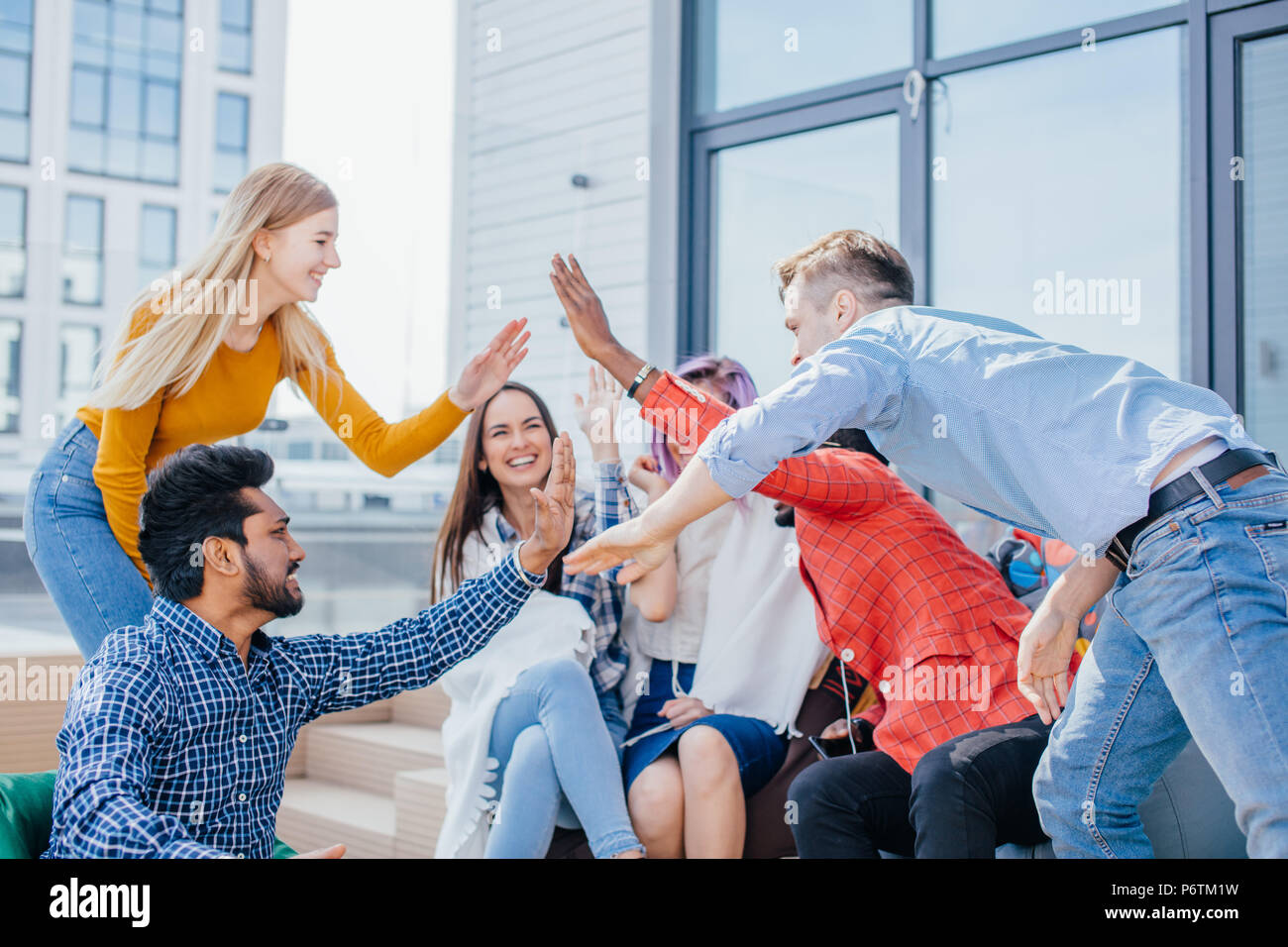 Young friends giving high five after making a good deal and earning a lot of money on marketing targeting investigation - Stock Image