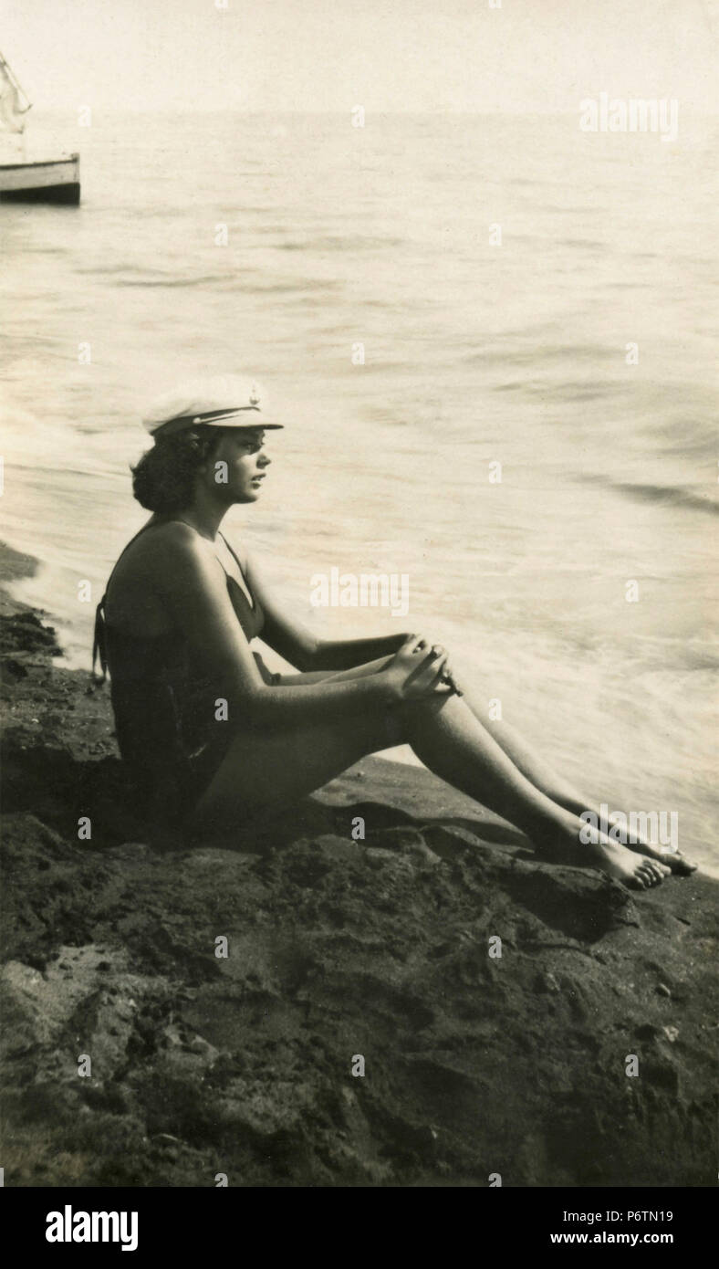 Girl on the beach with captain hat, 1930s - Stock Image
