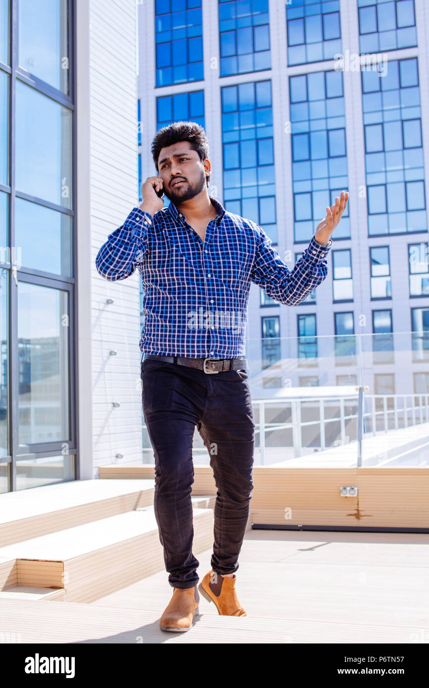 564d1d76b72 Indian young bearded businessman in casual wear walking and talking on cell  phone near business center
