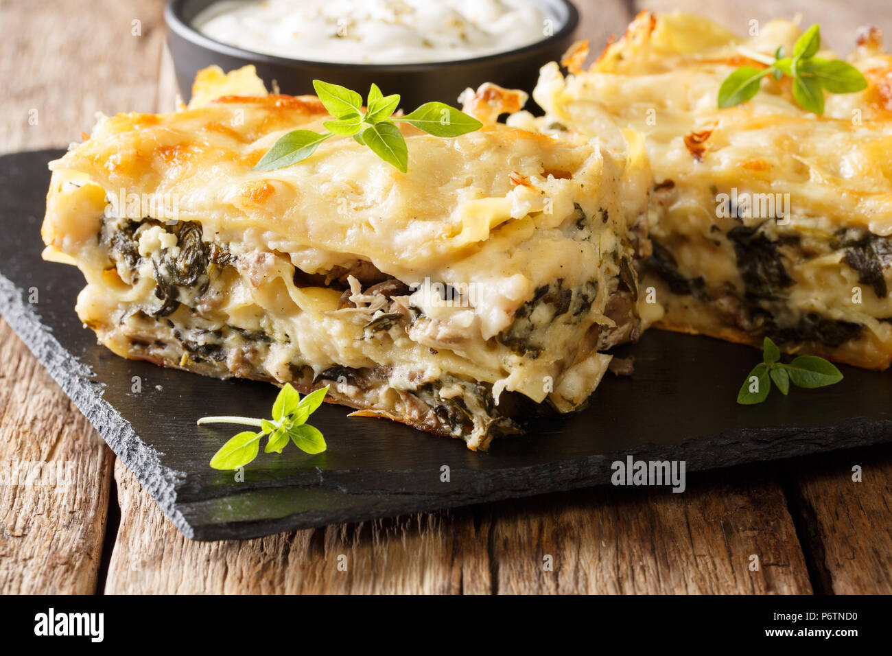 Homemade rustic lasagna with chicken, mushrooms, mozzarella and parmesan cheese and bechamel sauce closeup on a slate plate. horizontal Stock Photo