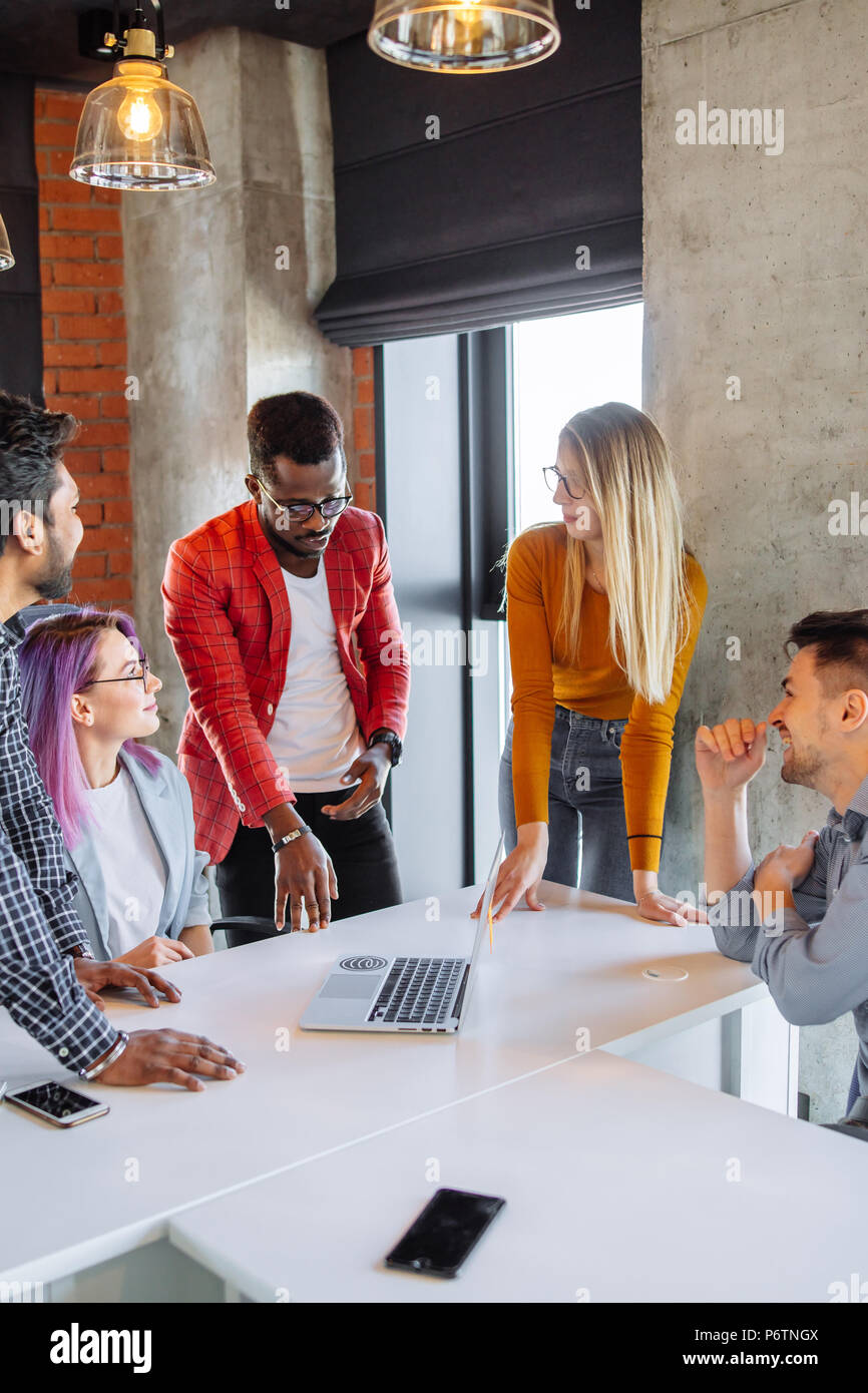 Diverse multiethnic group of young businesspeople in office boardroom gathering together around white table, discussing their business strategy and sh - Stock Image