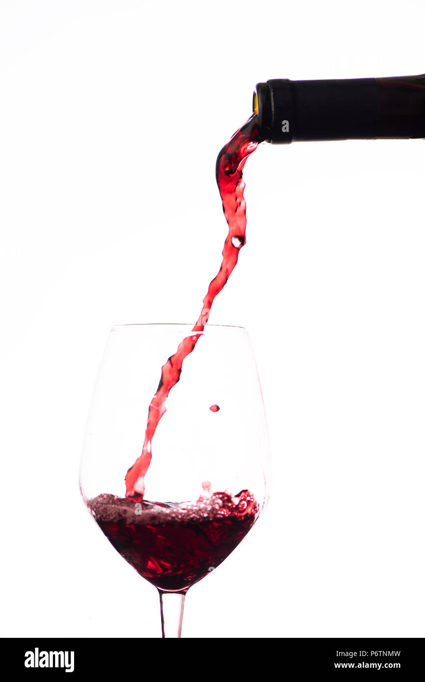 Red wine pouring in a wine glass, on a white background Stock Photo
