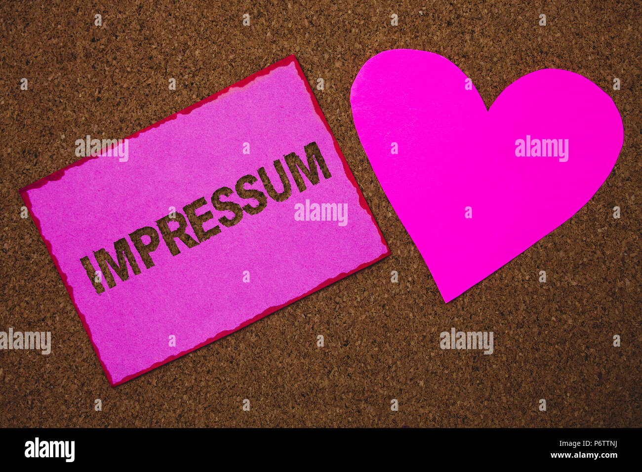 Handwriting text Impressum. Concept meaning Impressed Engraved Imprint German statement ownership authorship Paper heart ideas messages cork backgroun - Stock Image