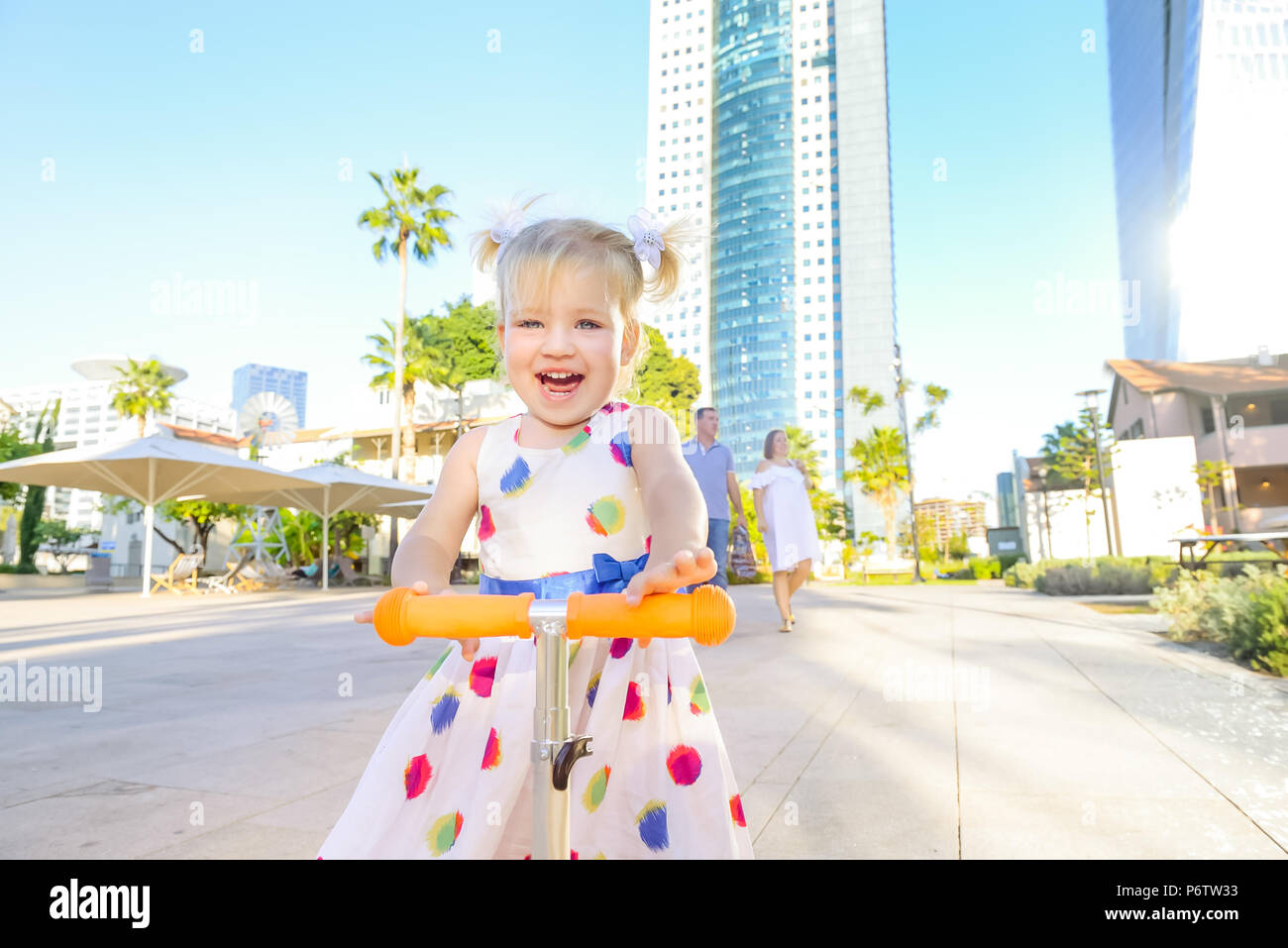 Emotional cute little blondy toddler girl in dress riding scooter in the city park recreation area with modern skyscraper buildings on the background. - Stock Image