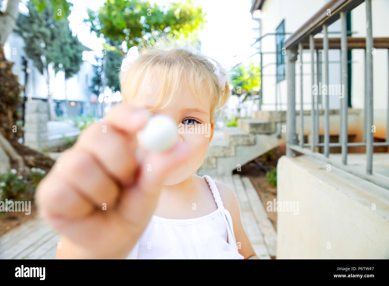 Close up cute little blondy toddler girl in white dress giving small sweet round candy for you. Selective focus. Copy space - Stock Image