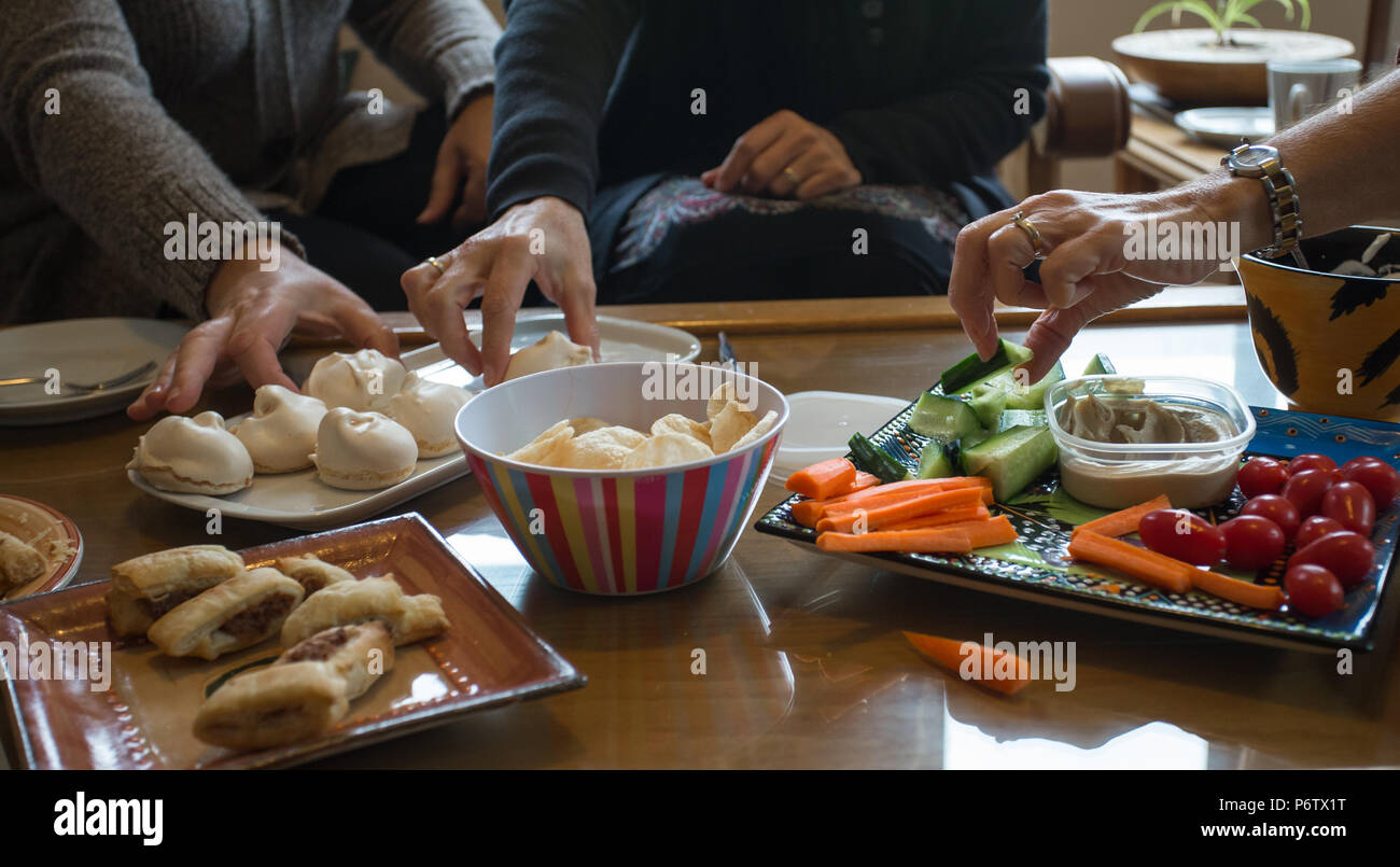ladies hands reaching out to pickup food on a full table of eats at a tea party - Stock Image