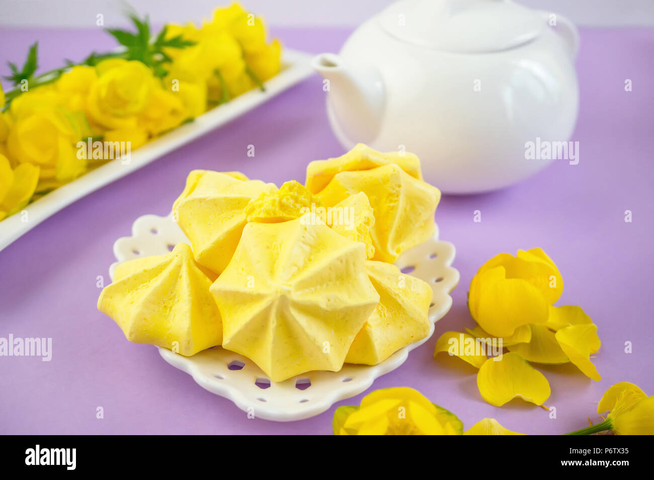 Yellow meringue on a lilac background in a tea serving with a white kettle. Stock Photo