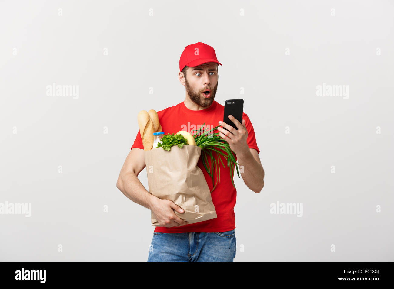 Delivery man holding paper bag with food and shock or angry with something in mobile phone on white background - Stock Image