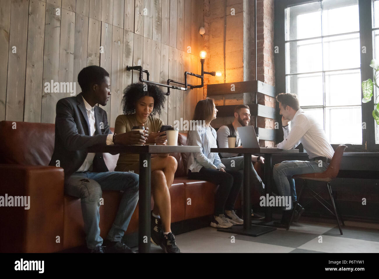 Multiracial millennials enjoying coffee working on gadgets in co - Stock Image