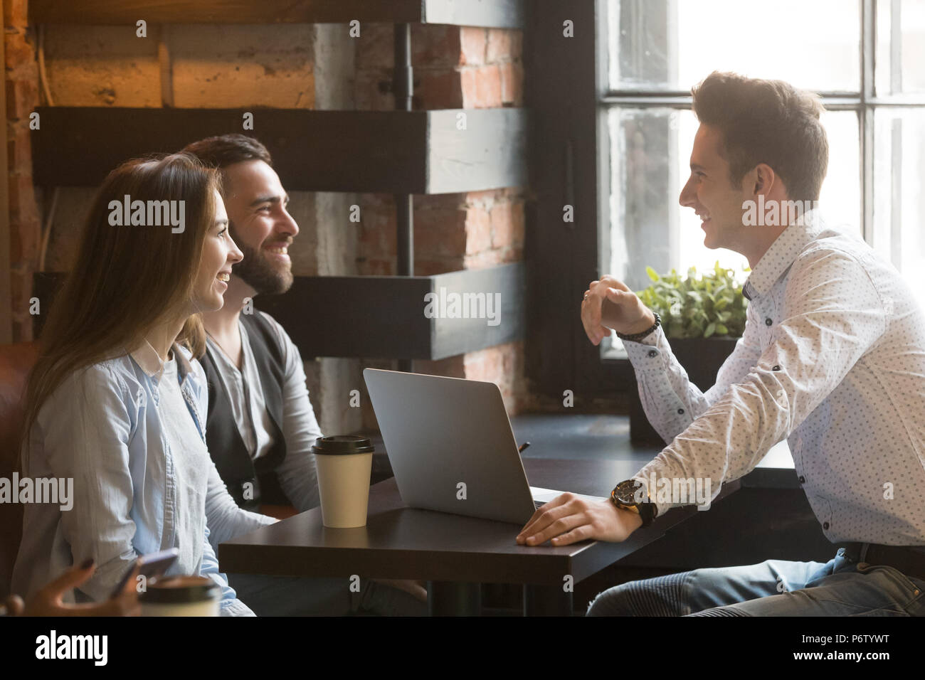 Male architect consulting excited millennial couple in coffee sh - Stock Image
