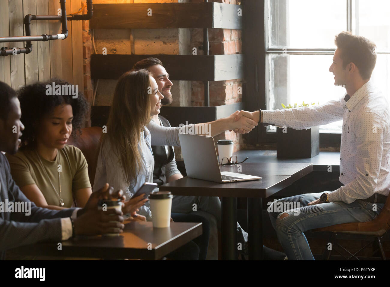 Smiling male broker greeting customers with handshake at cafe me - Stock Image