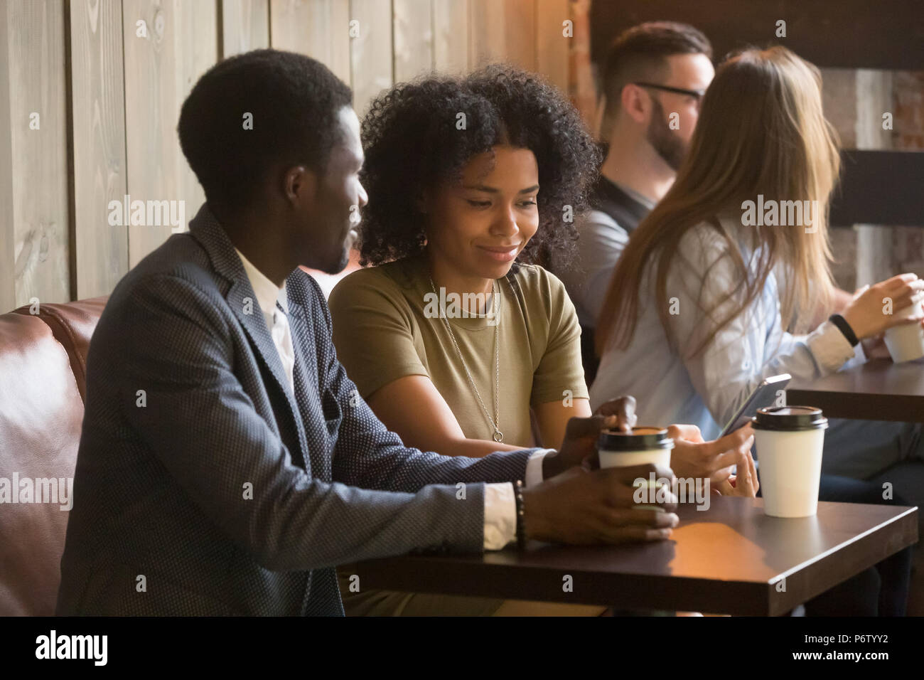 Multiracial people enjoying coffee to go during break in cafe - Stock Image