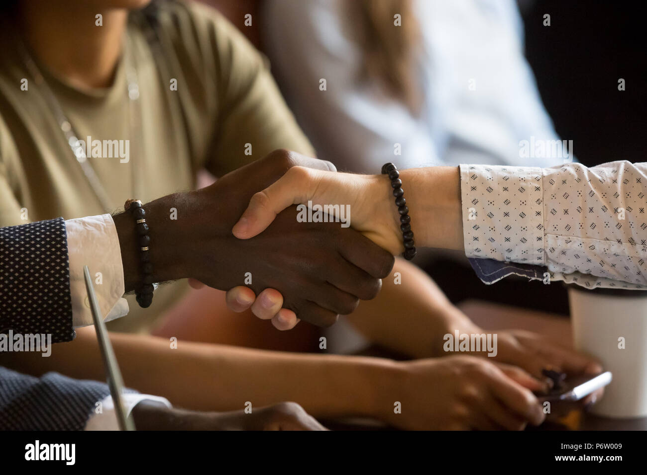Multiracial handshake greeting during business meeting in cafe - Stock Image