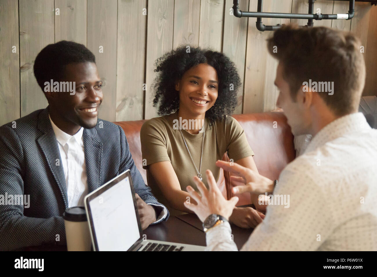 Caucasian architect consulting black clients out in coffee shop - Stock Image