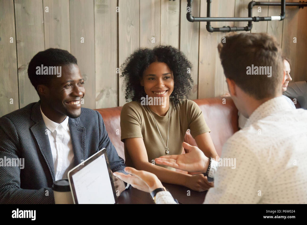 Caucasian consultant talking to black clients in coffee shop - Stock Image