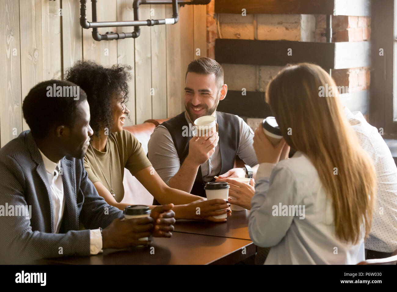 Smiling friends enjoying time together having coffee in cafe - Stock Image