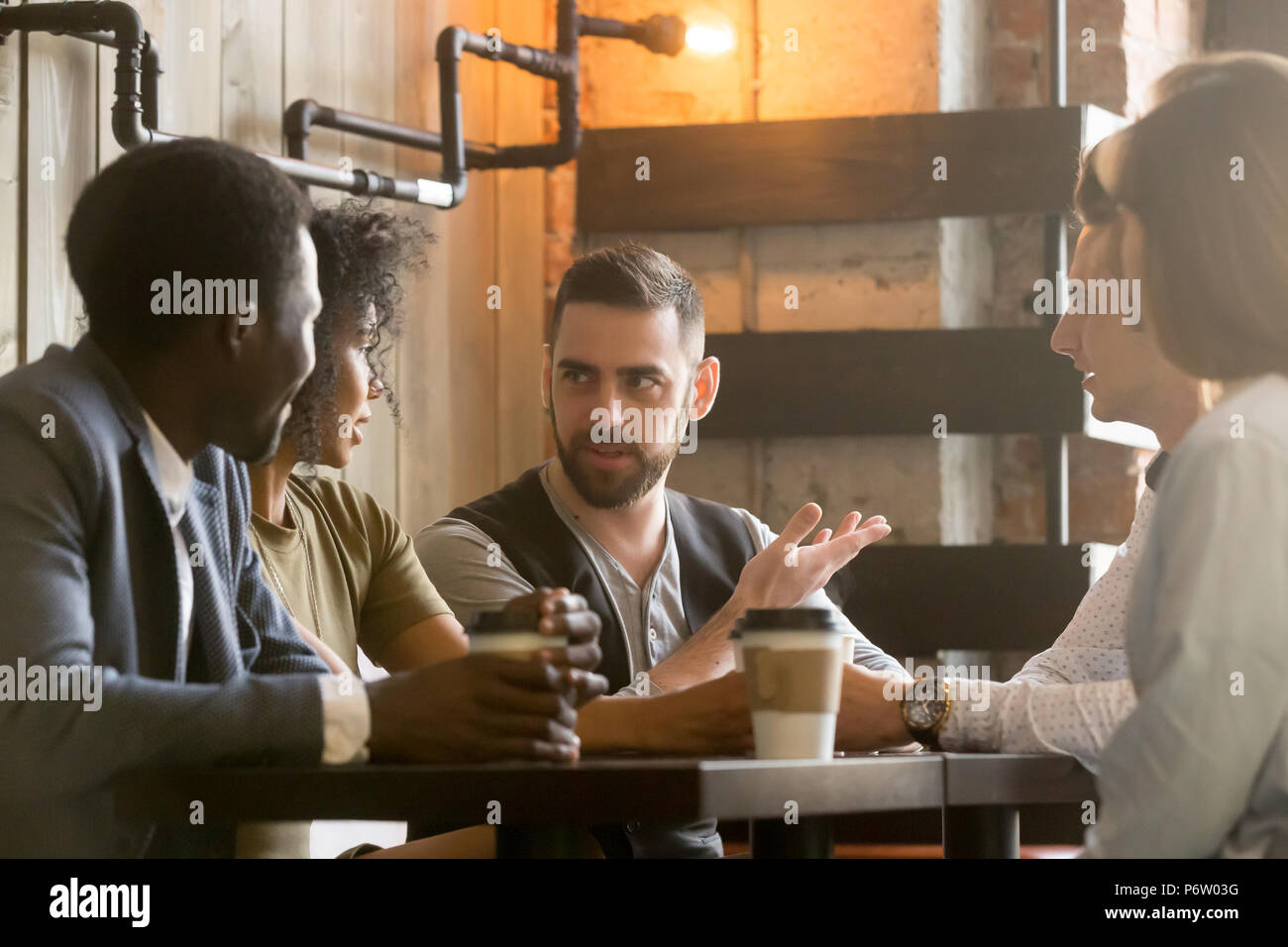 Multiracial colleagues discussing ideas during work break in caf - Stock Image