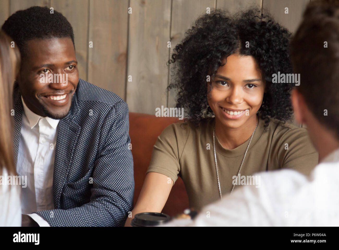Happy black friends enjoying meeting with colleagues out in cafe - Stock Image