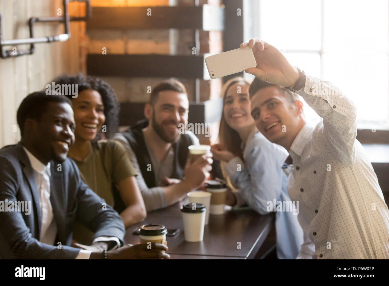 Millennial friends having fun making selfie in cafe - Stock Image