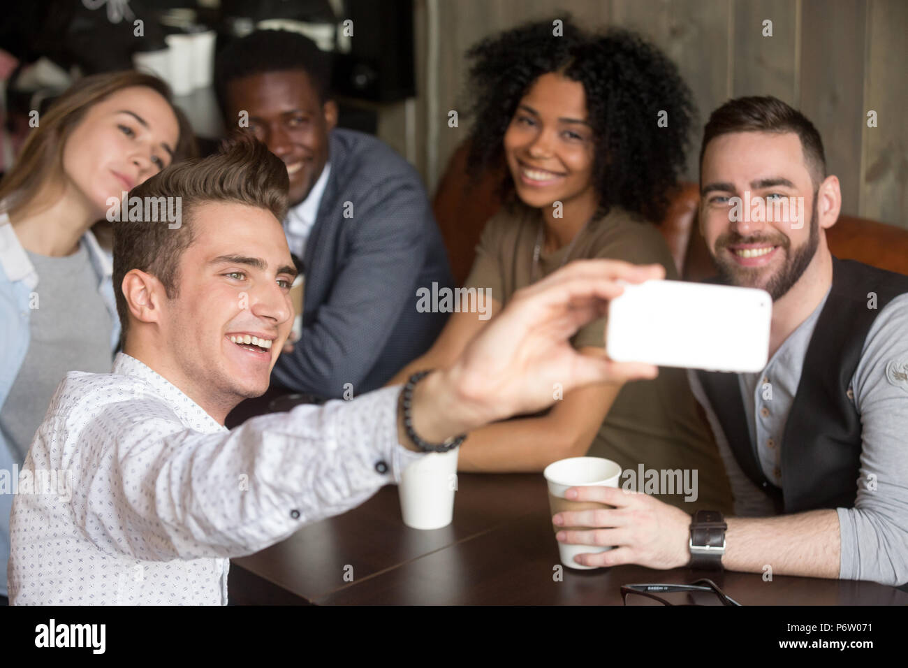 Diverse colleagues smiling for group photo resting in cafe - Stock Image
