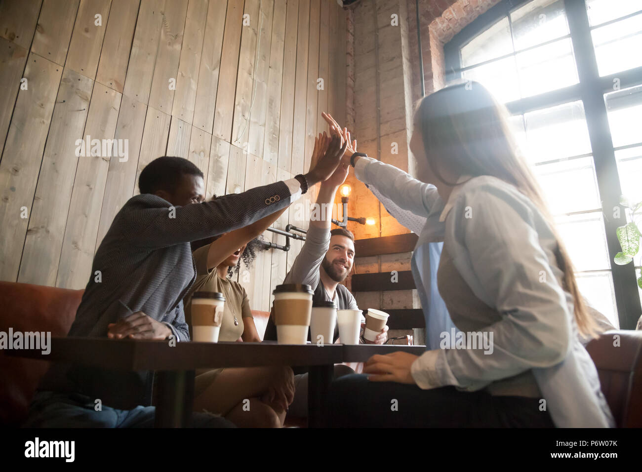 Happy diverse friends giving high five chilling out in cafe - Stock Image