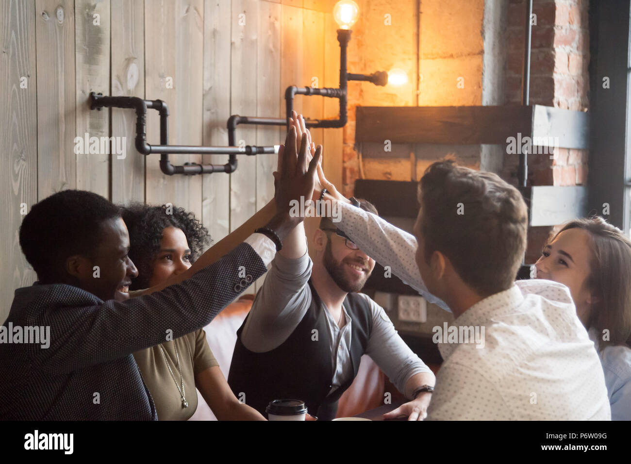 Smiling millennials giving high five during meeting in cafe - Stock Image