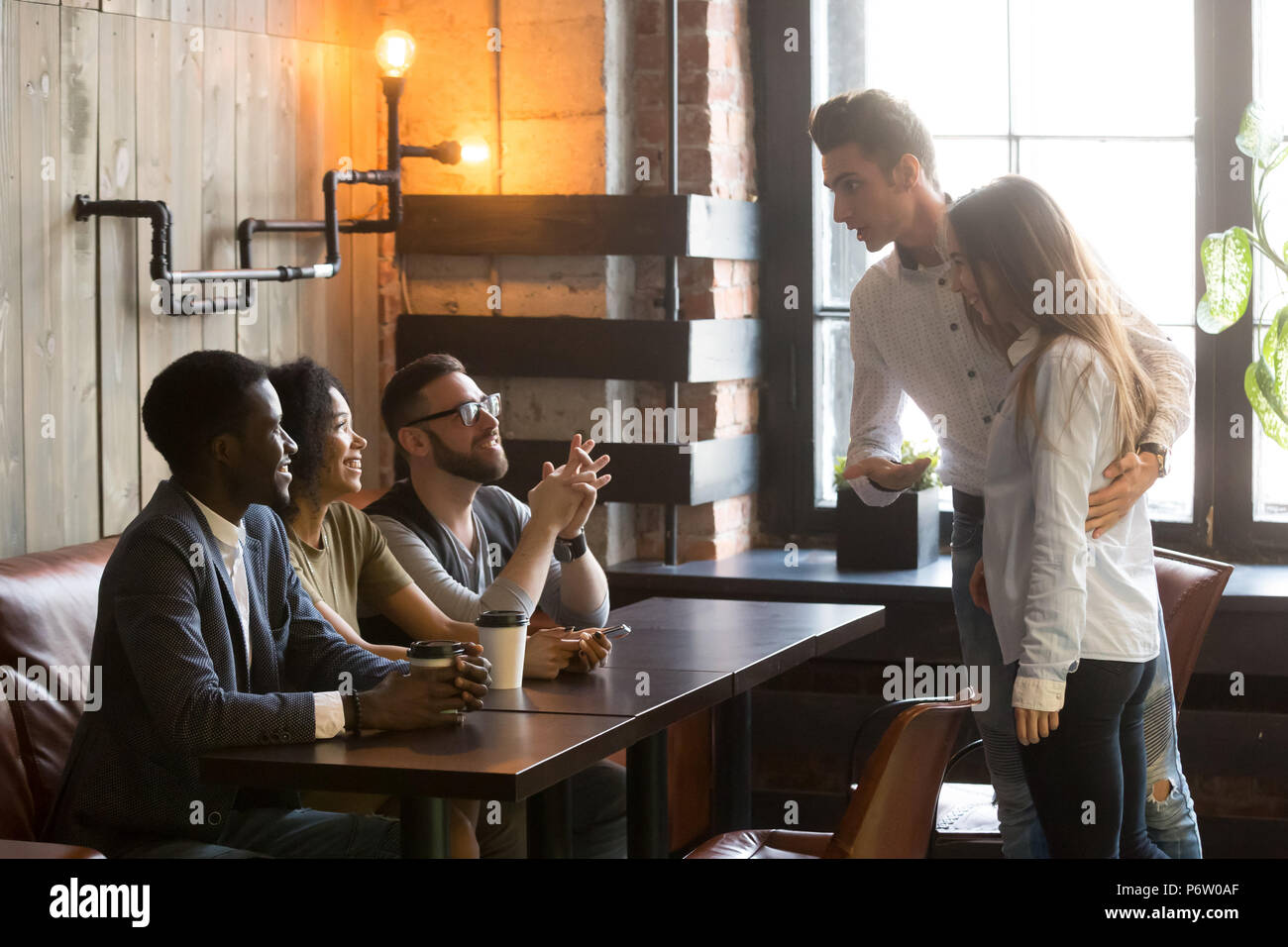 Caucasian man introducing girlfriend to friends at cafe - Stock Image