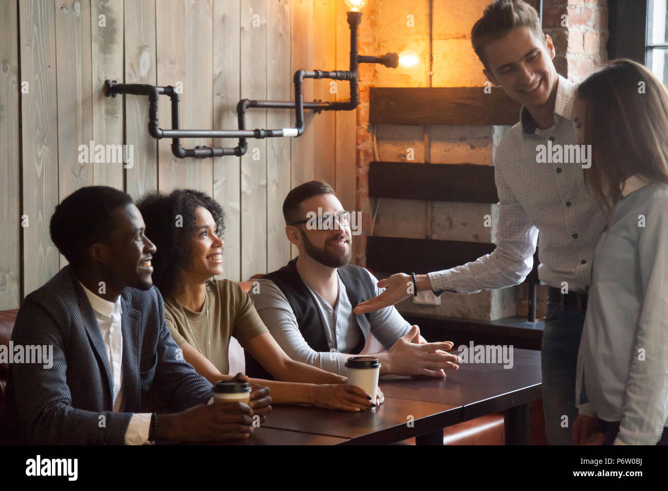 Smiling worker introducing new employee to colleagues during caf - Stock Image