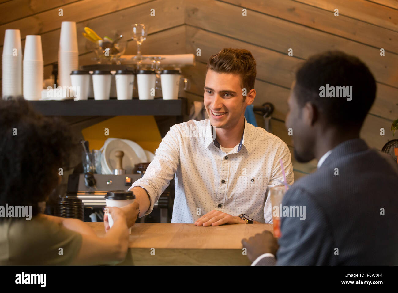 Caucasian barista serving coffee to black girl during date - Stock Image