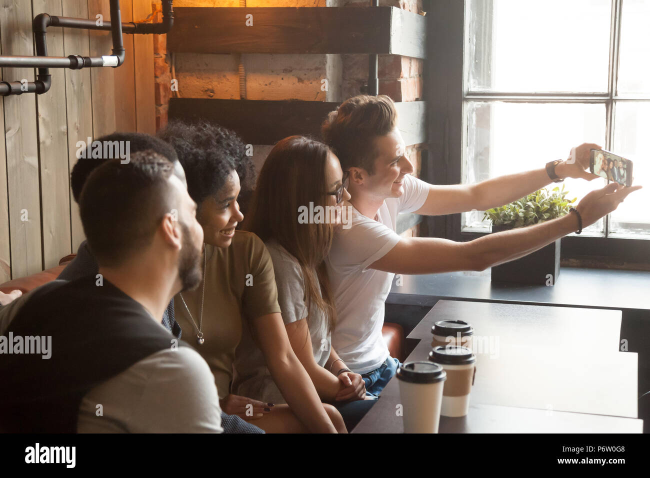 Happy multiracial friends making self-portrait during meeting in - Stock Image